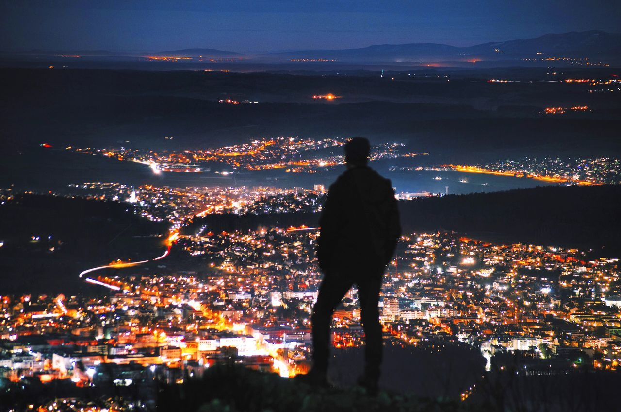 Silhouette of person standing in city at night