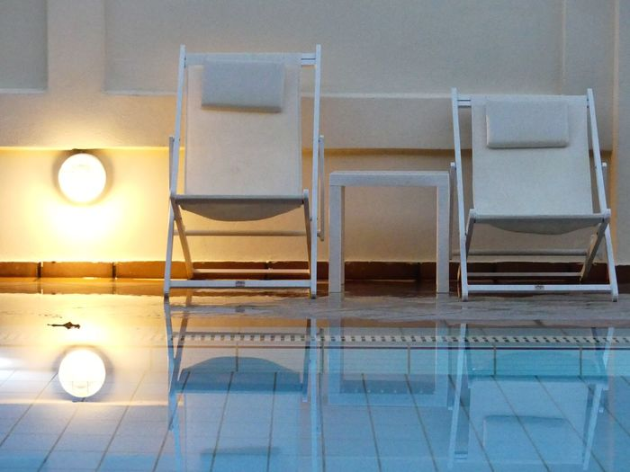 Empty chairs and tables in illuminated room