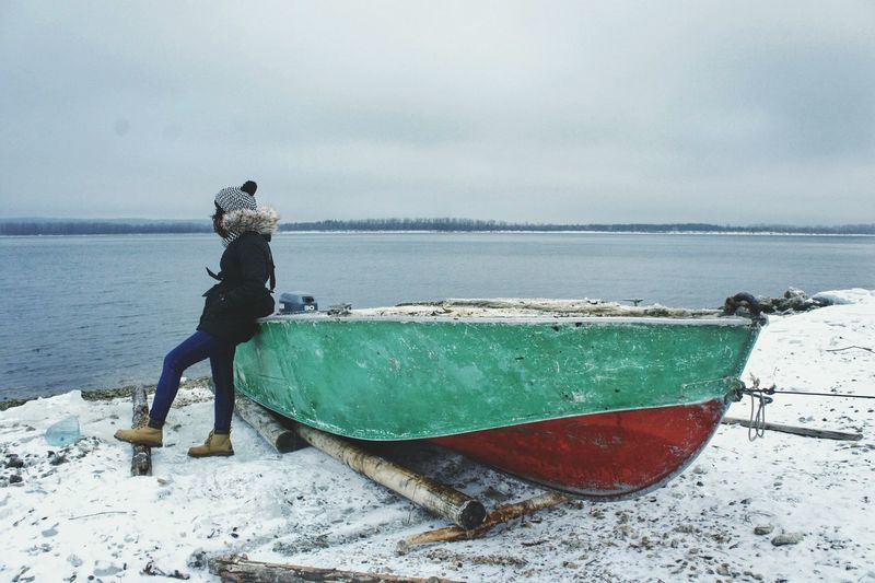 Side view of woman standing by boat at volga river