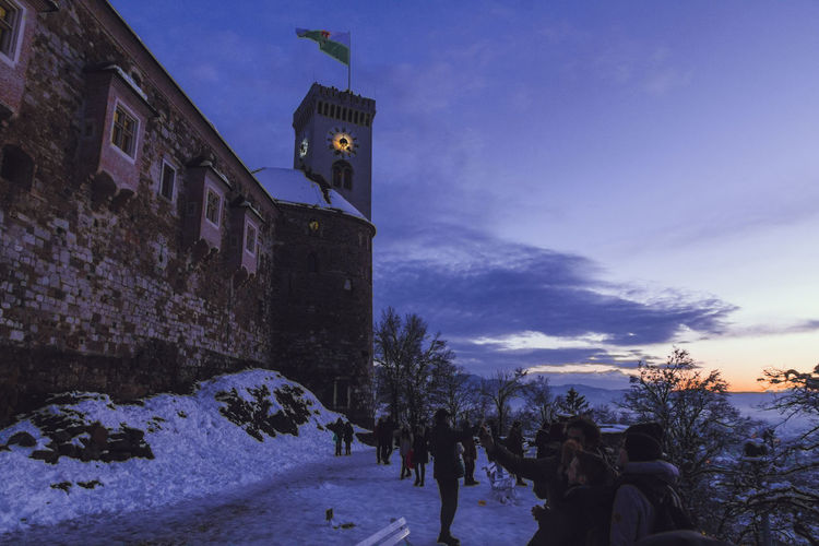 Castle Architecture Bluehour Building Exterior Built Structure Cold Temperature Day Human Representation Large Group Of People Low Angle View Nature Outdoors Real People Sky Snow Tower Tree Weather Winter