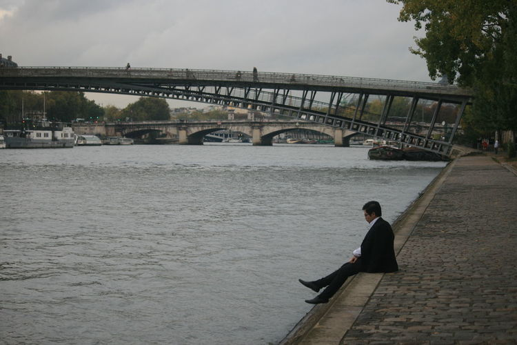 Businessman sitting on footpath by river with arch bridges in background