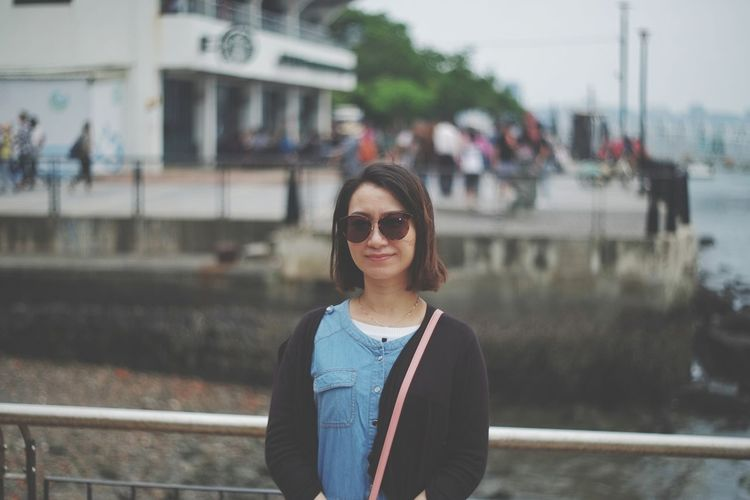 Portrait of smiling woman standing by railing in city