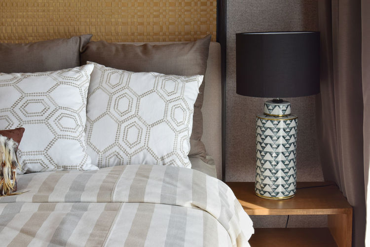 Pillows on bed by electric lamp at home