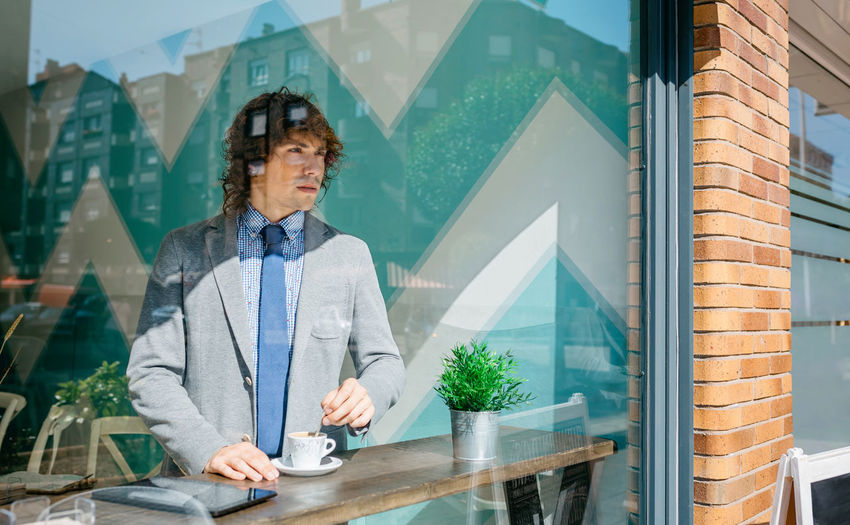 Young man looking through window at cafe
