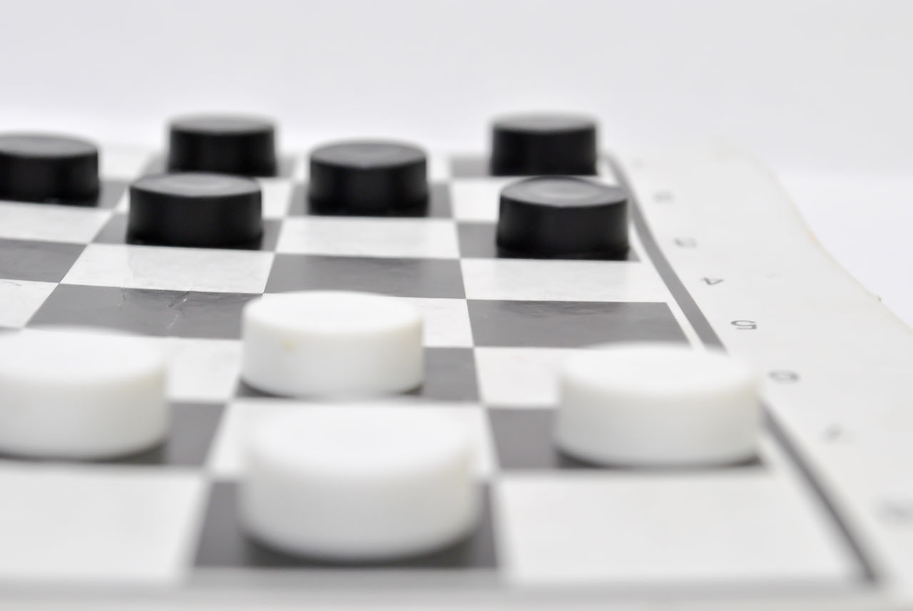 Close-Up Of Checkers Against White Background