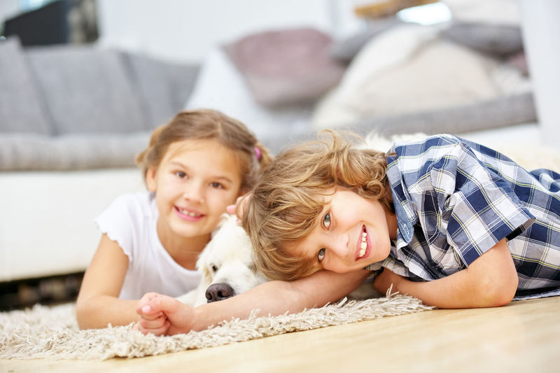 Portrait of happy siblings lying on hardwood floor at home