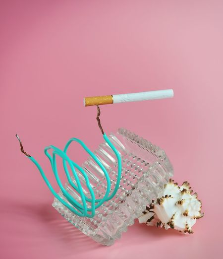 Close-up of cable and cigarette and ashtray against pink background
