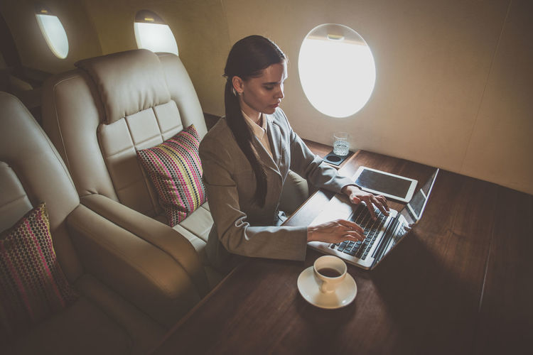 High angle view businesswoman using laptop in airplane