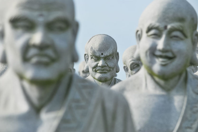Close-up of statues against sky