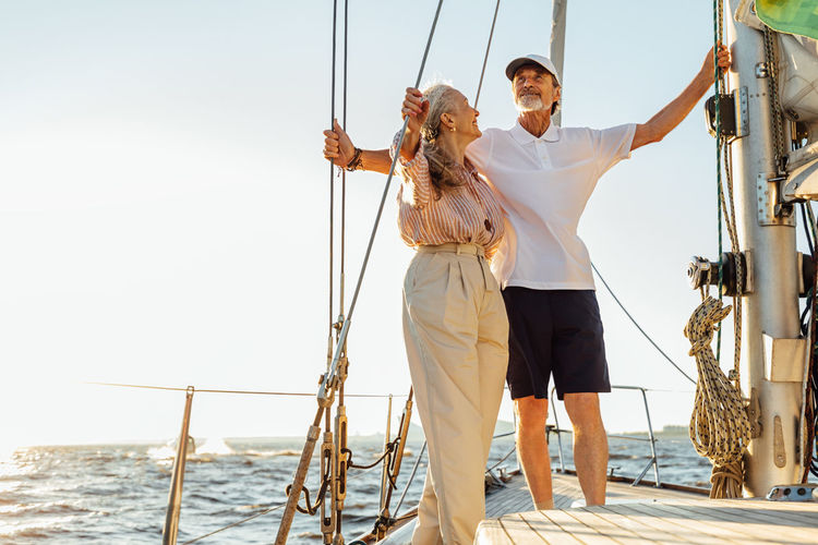 Low angel view of couple standing on sailboat against sea