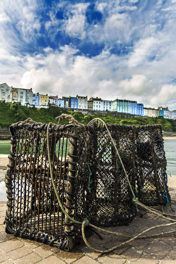 Wet lobster trap on footpath by harbor against cloudy sky
