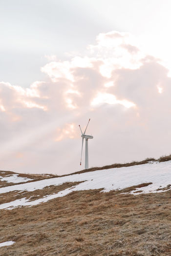Windmill on field against sky during winter