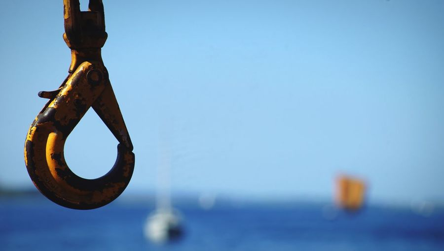 Close-up of iron hook against clear blue sky
