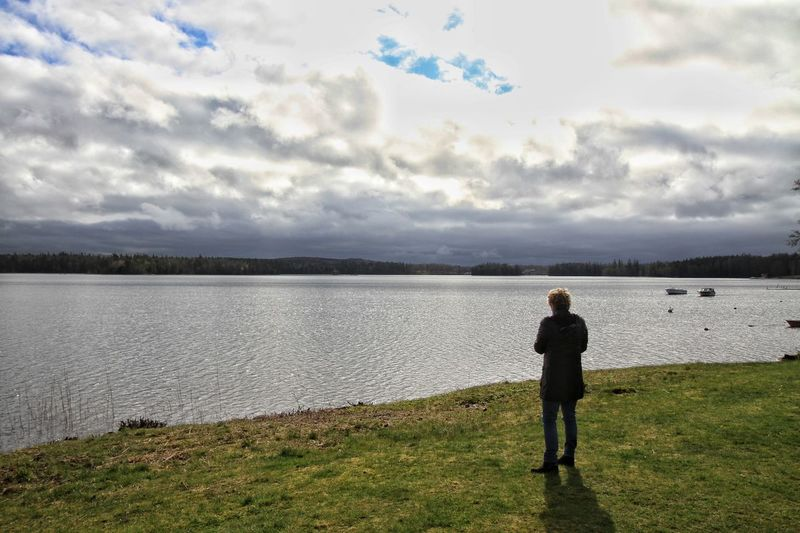 Rear view of man standing on field by lake against cloudy sky