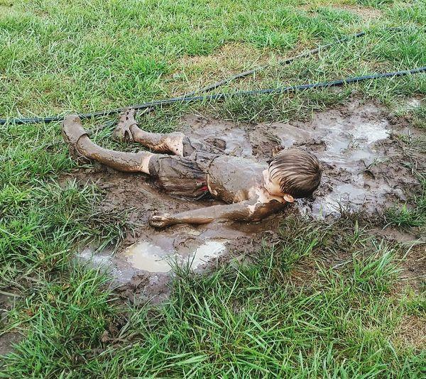 High angle view of playful muddy boy lying on grassy field