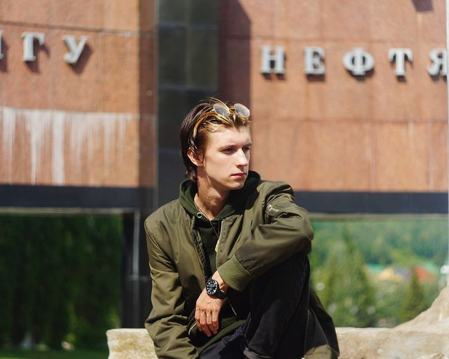 Young man looking away while sitting outdoors
