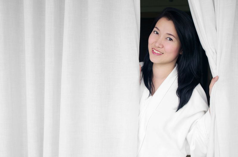 Asian woman smiling wearing a white robe, opened the curtains in the room. Robe White Woman Bath Bathrobe Beautiful Young Spa Female Girl Attractive Beauty Lady Happy Gown Lifestyle person Fresh Care Relaxing Health Skin Shower Bathroom Smiling Standing Relaxation Wellness Opening Healthy Home Bedroom Curtain Curtains Window Open Drapery Fabric Interior Room