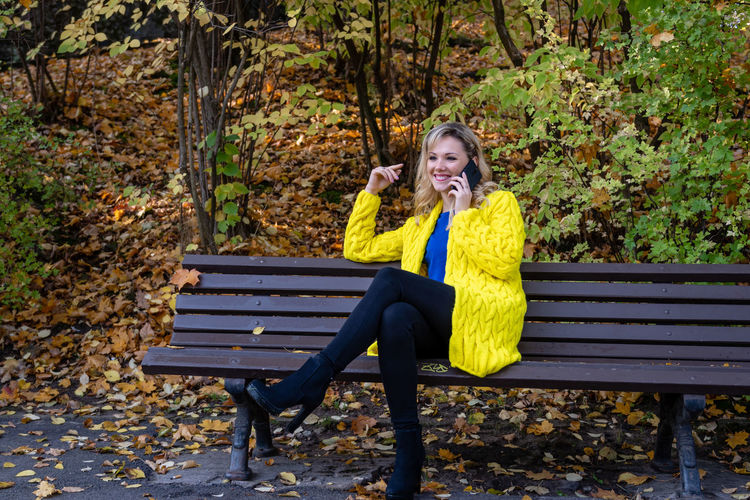 Full length of beautiful woman talking on phone while sitting on bench in park during autumn