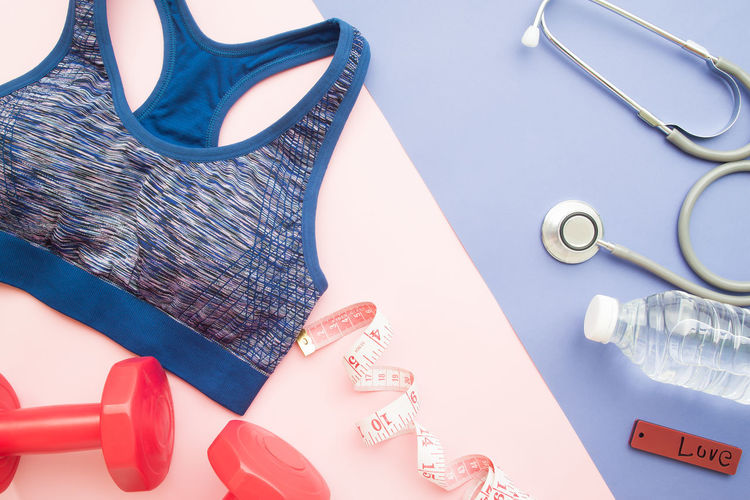 Healthy concept , diet plan with sport bra and bottle of water and Dumbbell on pastel background Beautiful Body & Fitness Care Diet Exercise Slim Sportbra Work Active Concept Dumbbell Fitness Gym Healthy Heart Lifestyles Pastel Sport Sportwear Stethoscope  Strong Tape Training Water Weight