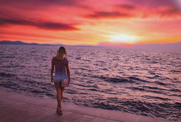 Rear view of woman standing on promenade against orange sky