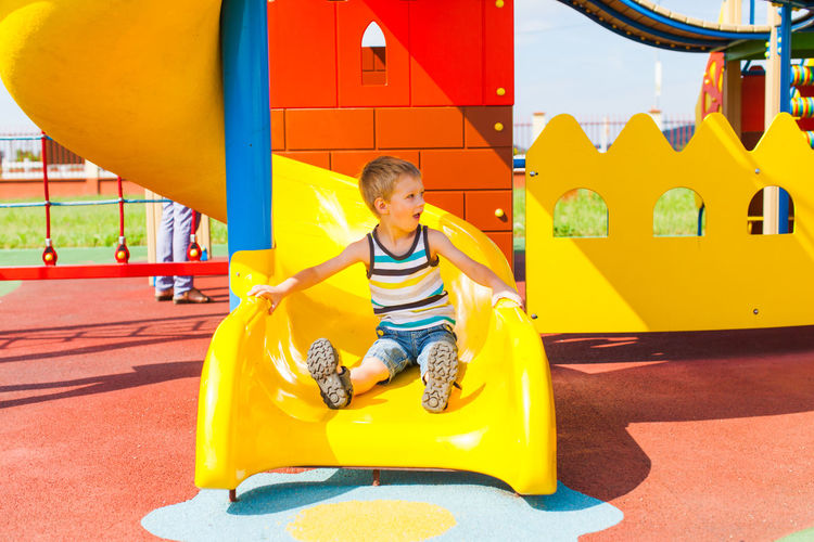Full length of boy sitting on yellow playground