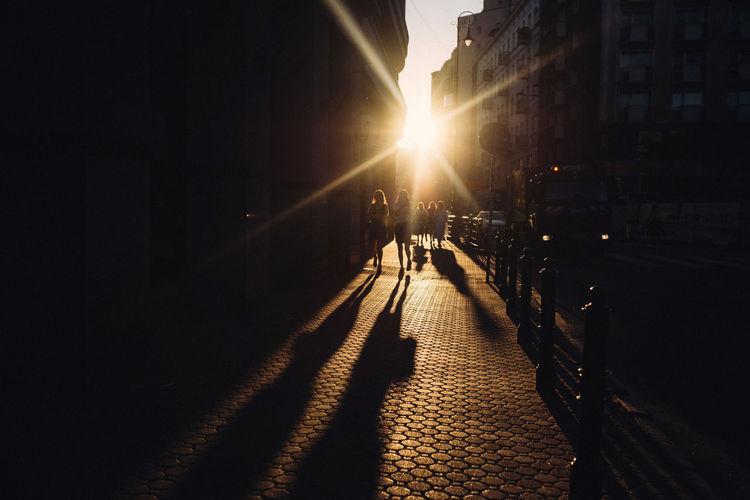 Silhouette people walking on footpath in city