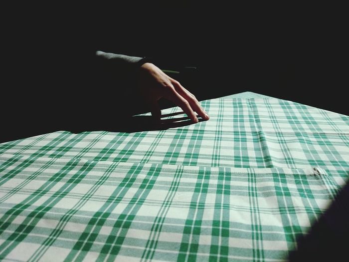 Close-up of a hand on chequered table cloth