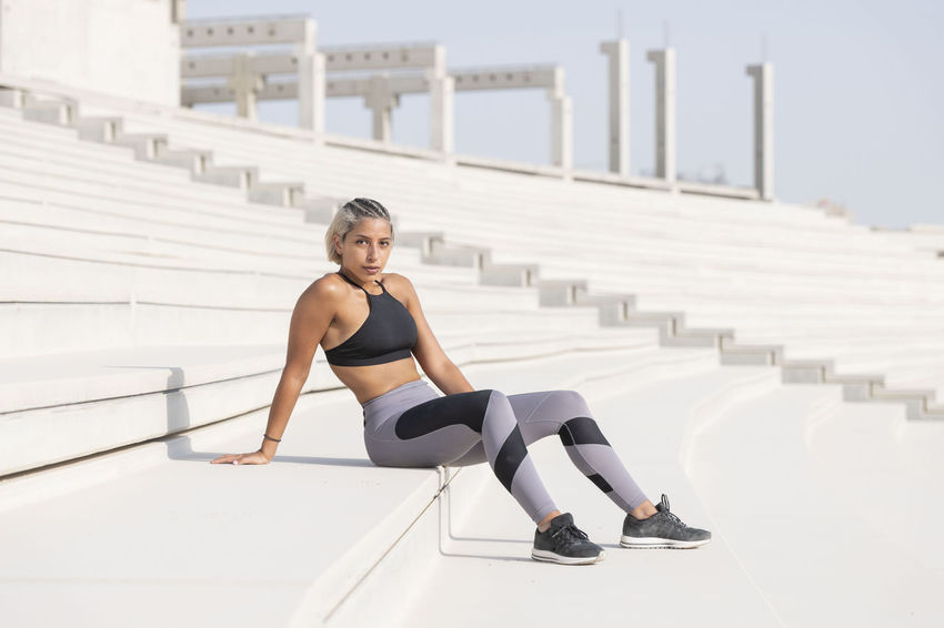 Middle Eastern Girl with short braided hair sitting on the stairs of a construction site wearing gray and black fitness outfit on a hot bright sunny day. Exercising Jumping Off Rocks Sitting Architecture Bright Day Built Structure Day Dusty Exercising Fitness Model Focus On Foreground Full Length Hot Day ☀ Leisure Activity Lifestyles Looking At Camera Middle Eastern Woman Nature One Person Outdoors Portrait Railing Real People Sitting Sport Sports Clothing Stretching Teenager Young Adult Young Women