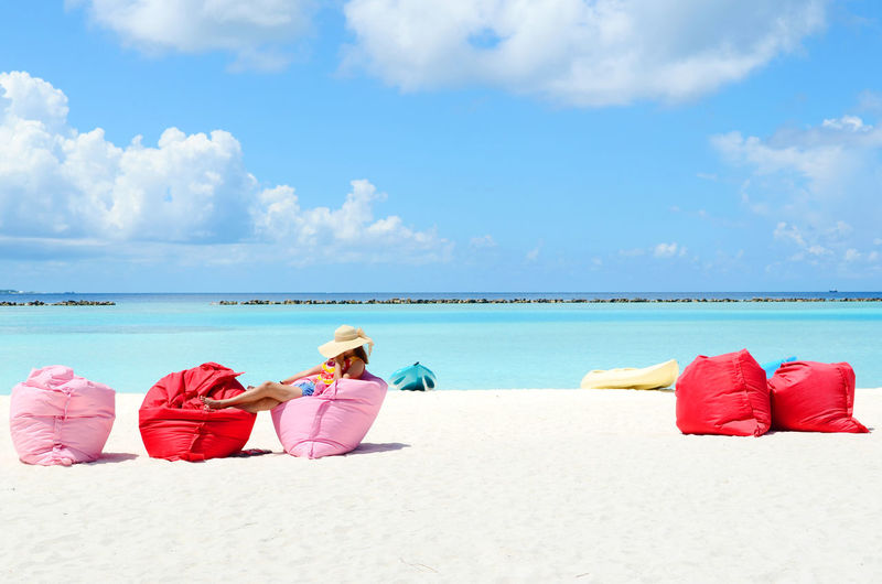 Woman Resting On Bean Bags At Beach Against Sky During Sunny Day