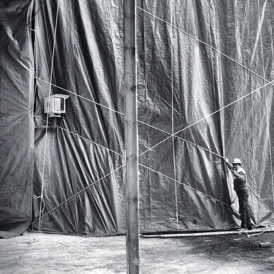 A worker minding the ropes holding the plastic drapes from covering the timelapse camera box. Grid Worker Photooftheday Timelapse Bnw Bnwphotography