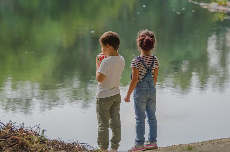 Curiousity Bonding Boy And Girl Casual Clothing Childhood Day Friendship Full Length Girls Lake Lakeshore Leisure Activity Lifestyles Nature Outdoors Real People Rear View Sibling Standing Togetherness Two People Water Young Adult Young Women