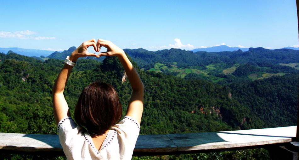 Rear view of woman making heart shape against mountains