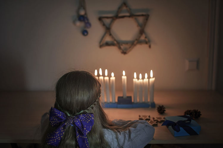 Rear view of girl looking at burning candles against wall at home