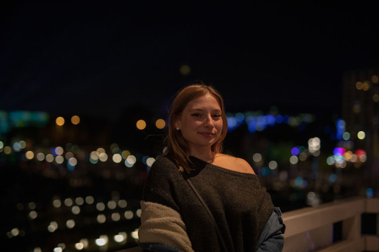 Portrait of smiling young woman standing in city at night