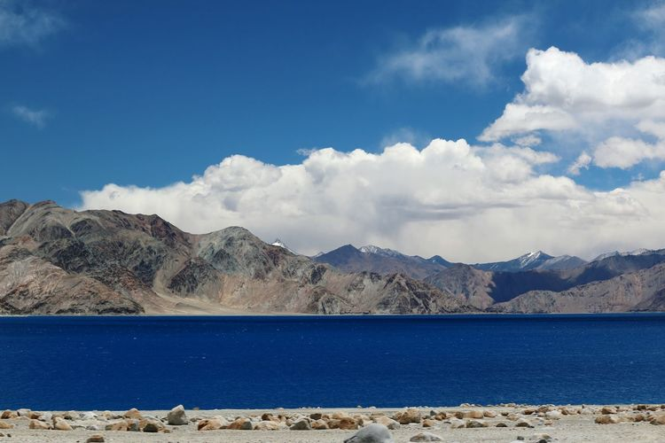 Scenic view of lake against mountains and blue sky