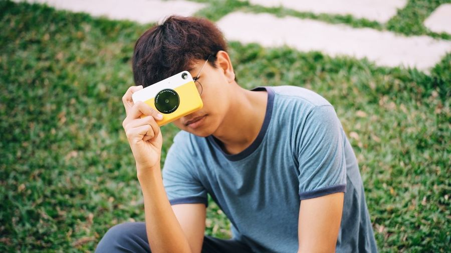 Young man photographing with camera on field