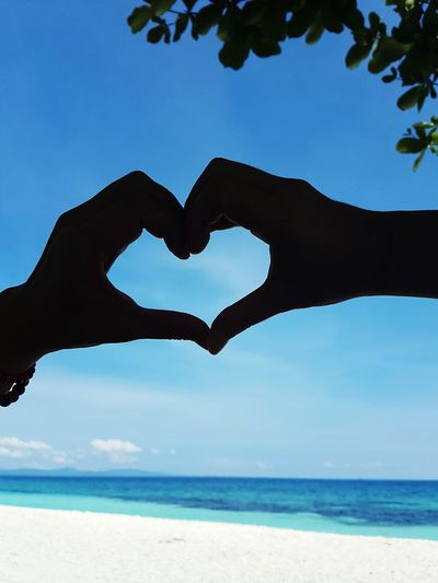 Silhouette of hands making heart shape against sky