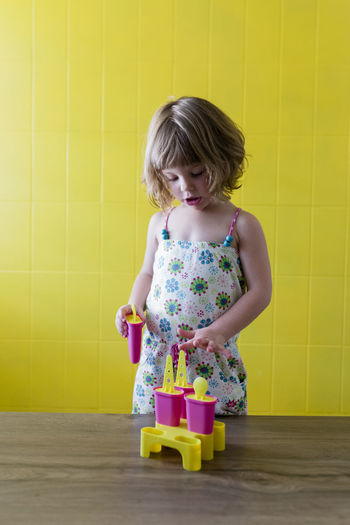Cute girl playing with toys on table against yellow wall