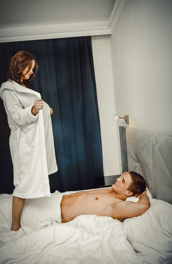 Shirtless man looking at woman undressing bathrobe on bed at home