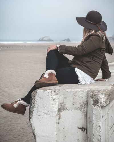 Side view of woman sitting on railing at beach