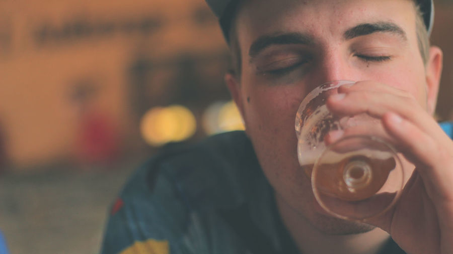 Close-up of young man with eyes closed drinking beer in glass