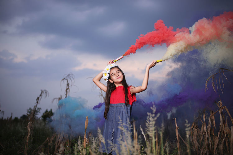 Smiling cute girl holding distress flares while standing against sky at dusk