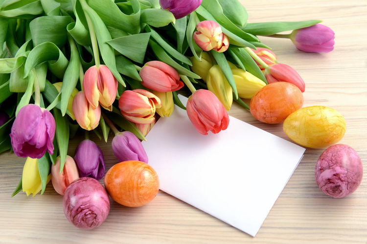 Close-up of tulips and greeting card with easter eggs on table