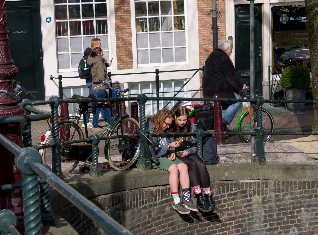 bicycle, transportation, building exterior, built structure, architecture, mode of transport, real people, land vehicle, cycling, full length, day, riding, outdoors, lifestyles, city, women, men, bicycle rack, biker, adult, people