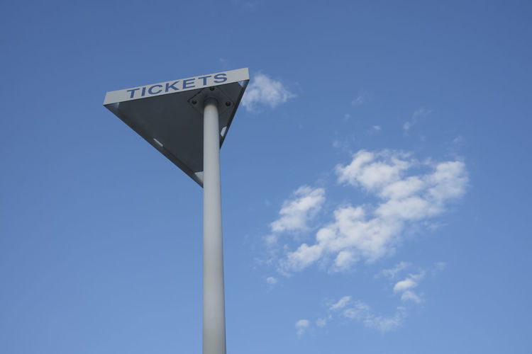 Low angle view of sign against sky