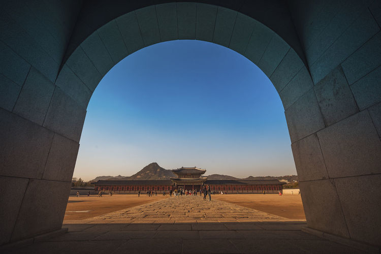 People visiting temple against clear blue sky seen through tunnel