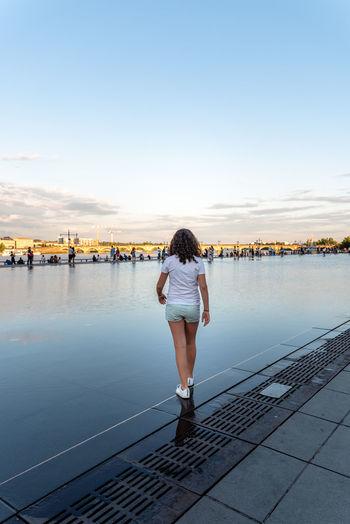 Rear view of teenage girl walking in city against sky
