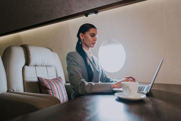 Businesswoman using laptop in airplane