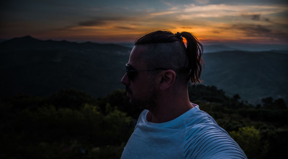 Portrait of mature man against mountains during sunset