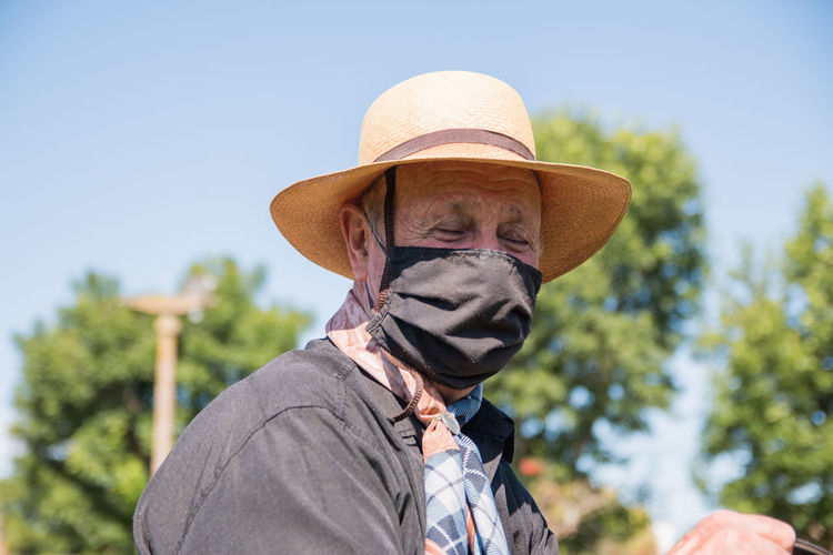 Portrait of elder man wearing hat against sky